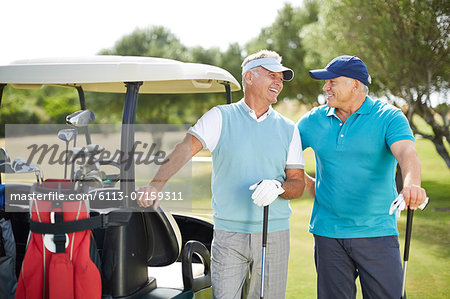 Senior men laughing next to golf cart Stock Photo - Premium Royalty-Free, Image code: 6113-07159311