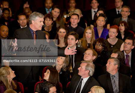 Theater audience watching standing man gesturing Stock Photo - Premium Royalty-Free, Image code: 6113-07159361