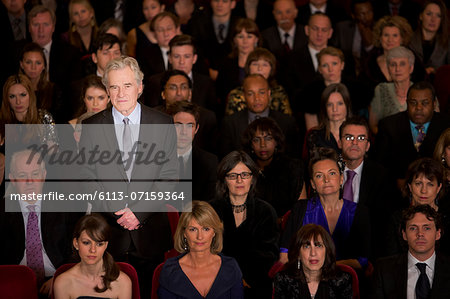 Serious man standing in theater audience Stock Photo - Premium Royalty-Free, Image code: 6113-07159364