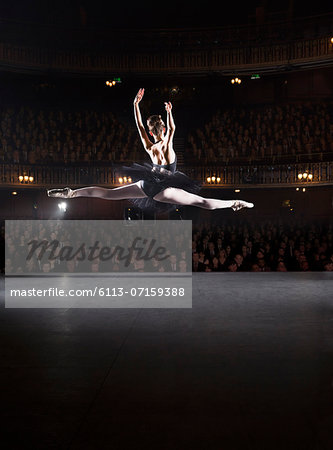 Ballerina mid-air on theater stage Stock Photo - Premium Royalty-Free, Image code: 6113-07159388