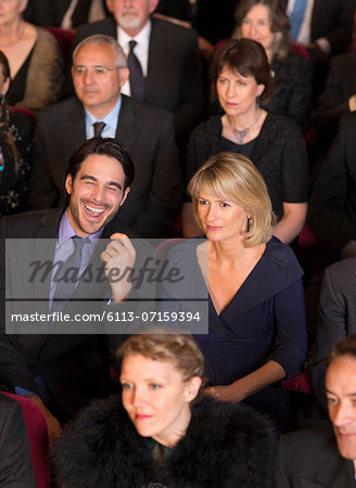 Man laughing among serious theater audience Stock Photo - Premium Royalty-Free, Image code: 6113-07159394