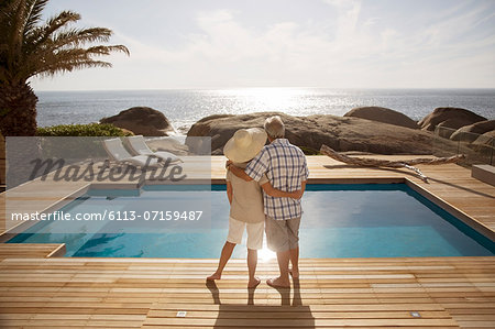 Senior couple hugging by modern pool overlooking ocean Stock Photo - Premium Royalty-Free, Image code: 6113-07159487