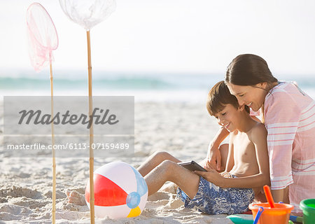 Mother and son relaxing on beach Stock Photo - Premium Royalty-Free, Image code: 6113-07159489