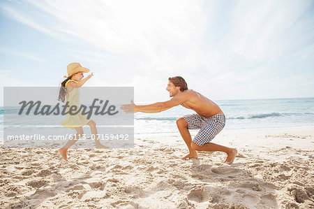 Father and daughter playing on beach Stock Photo - Premium Royalty-Free, Image code: 6113-07159492