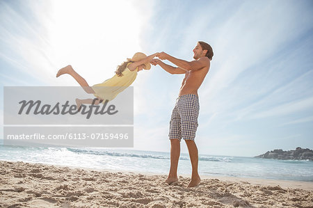 Father and daughter playing on beach Stock Photo - Premium Royalty-Free, Image code: 6113-07159496