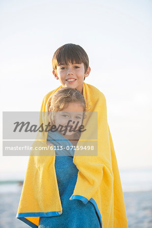 Brother and sister wrapped in towels on beach Stock Photo - Premium Royalty-Free, Image code: 6113-07159498