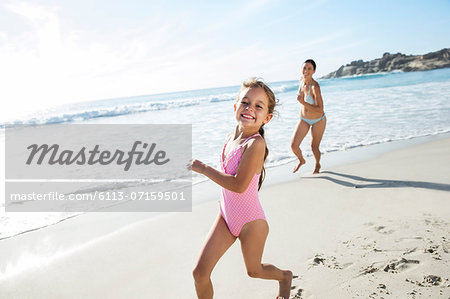 Mother and daughter running on beach Stock Photo - Premium Royalty-Free, Image code: 6113-07159501
