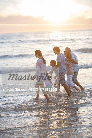 Multi-generation family walking in surf at beach Stock Photo - Premium Royalty-Free, Image code: 6113-07159503