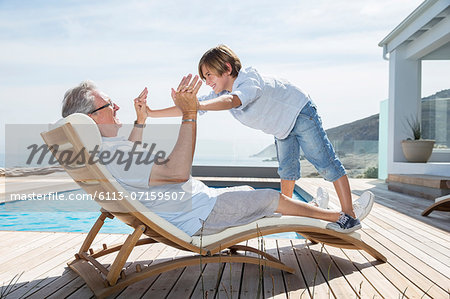 Grandfather and grandson playing at poolside Stock Photo - Premium Royalty-Free, Image code: 6113-07159507
