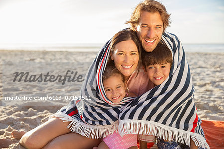 Family wrapped in blanket on beach Stock Photo - Premium Royalty-Free, Image code: 6113-07159511