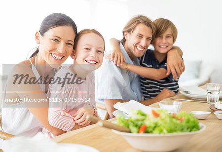 Family sitting together at table Stock Photo - Premium Royalty-Free, Image code: 6113-07159514