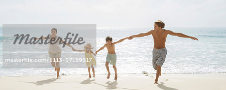 Family running together on beach Stock Photo - Premium Royalty-Free, Image code: 6113-07159517