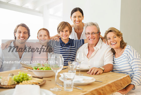 Multi-generation family smiling together at table Stock Photo - Premium Royalty-Free, Image code: 6113-07159526