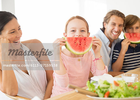 Family eating watermelon at table Stock Photo - Premium Royalty-Free, Image code: 6113-07159538