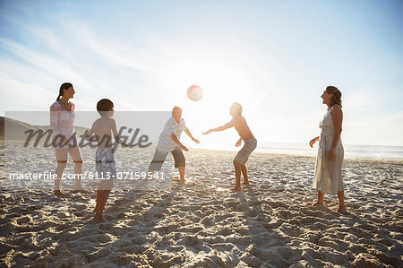 Multi-generation family playing volleyball on beach Stock Photo - Premium Royalty-Free, Image code: 6113-07159541
