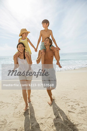 Parents carrying children on shoulders at beach Stock Photo - Premium Royalty-Free, Image code: 6113-07159548