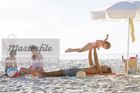 Family relaxing together on beach Stock Photo - Premium Royalty-Free, Image code: 6113-07159550