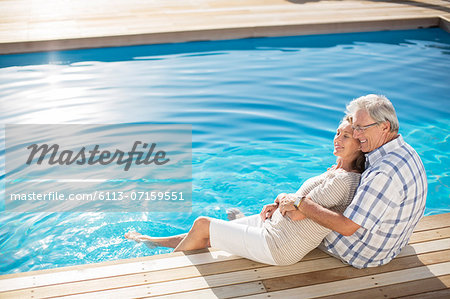 Senior couple relaxing by pool Stock Photo - Premium Royalty-Free, Image code: 6113-07159551