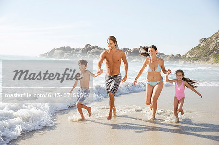 Family running together in waves Stock Photo - Premium Royalty-Free, Image code: 6113-07159564
