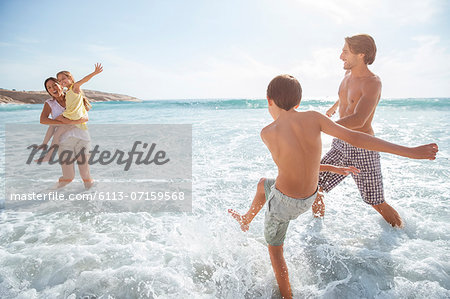 Family playing together in waves on beach Stock Photo - Premium Royalty-Free, Image code: 6113-07159568
