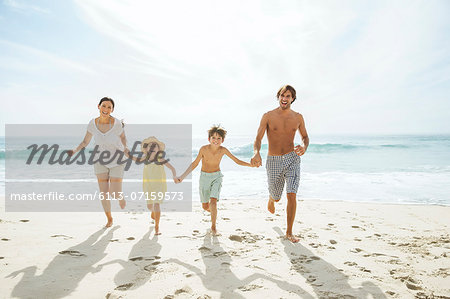 Family running together on beach Stock Photo - Premium Royalty-Free, Image code: 6113-07159573