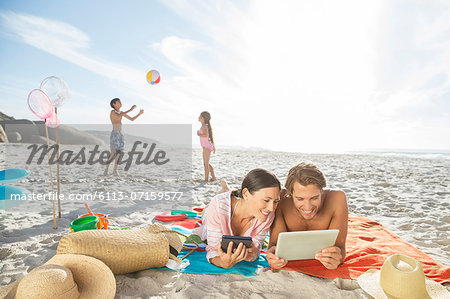 Family relaxing together on beach Stock Photo - Premium Royalty-Free, Image code: 6113-07159577