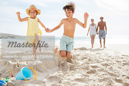 Children kicking down sandcastle on beach Stock Photo - Premium Royalty-Free, Image code: 6113-07159586
