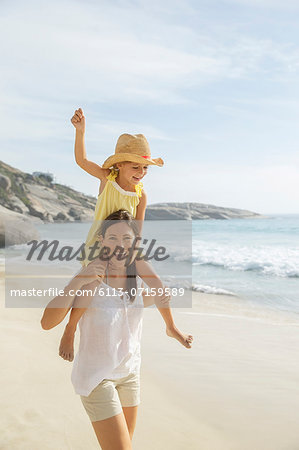 Mother carrying daughter on shoulders on beach Stock Photo - Premium Royalty-Free, Image code: 6113-07159589