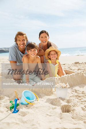 Family sitting in sandcastle on beach Stock Photo - Premium Royalty-Free, Image code: 6113-07159605