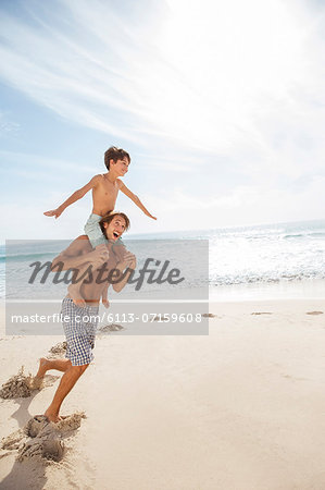Father and son playing on beach Stock Photo - Premium Royalty-Free, Image code: 6113-07159608