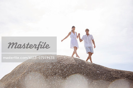 Couple walking on rock formation Stock Photo - Premium Royalty-Free, Image code: 6113-07159635