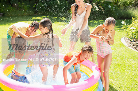 Family playing in paddling pool in backyard Stock Photo - Premium Royalty-Free, Image code: 6113-07159703