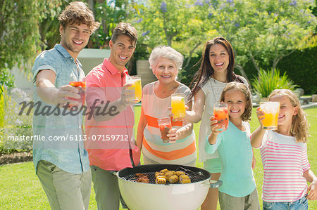 Family barbecuing together in backyard Stock Photo - Premium Royalty-Free, Image code: 6113-07159712
