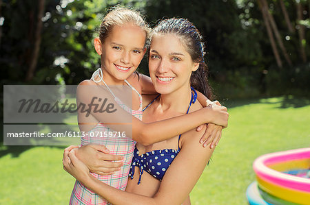 Mother and daughter hugging in backyard Stock Photo - Premium Royalty-Free, Image code: 6113-07159716