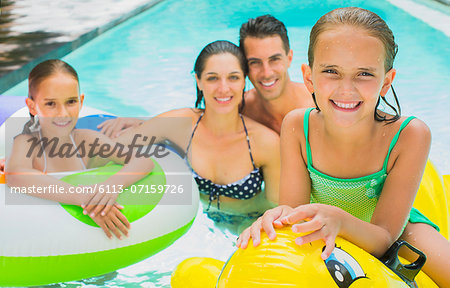 Family swimming together in pool Stock Photo - Premium Royalty-Free, Image code: 6113-07159726