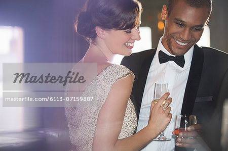 Well dressed couple drinking champagne and cocktail Stock Photo - Premium Royalty-Free, Image code: 6113-07159887