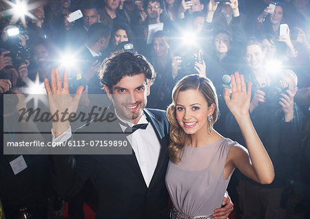 Celebrity couple waving on red carpet with paparazzi in background Stock Photo - Premium Royalty-Free, Image code: 6113-07159890