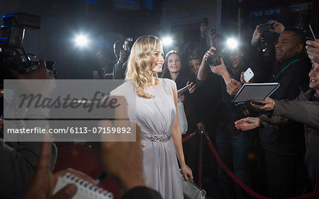Female celebrity posing for paparazzi on red carpet Stock Photo - Premium Royalty-Free, Image code: 6113-07159892
