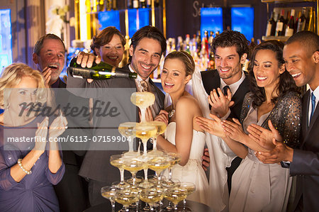 Bride and group pouring champagne pyramid at wedding reception Stock Photo - Premium Royalty-Free, Image code: 6113-07159904
