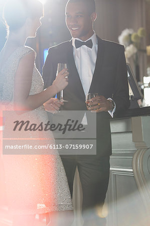 Well dressed couple talking and drinking champagne and cocktail Stock Photo - Premium Royalty-Free, Image code: 6113-07159907