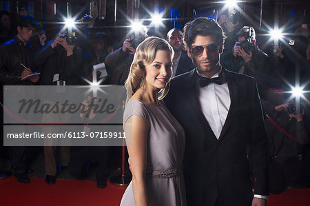 Serious celebrity couple on red carpet with paparazzi in background Stock Photo - Premium Royalty-Free, Image code: 6113-07159911