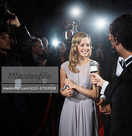 Celebrity being interviewed on red carpet Stock Photo - Premium Royalty-Free, Image code: 6113-07159918