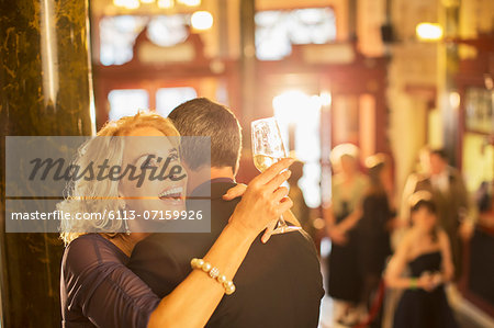 Enthusiastic woman with champagne hugging man in theater lobby Stock Photo - Premium Royalty-Free, Image code: 6113-07159926