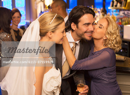 Mother kissing groom at wedding reception Stock Photo - Premium Royalty-Free, Image code: 6113-07159928