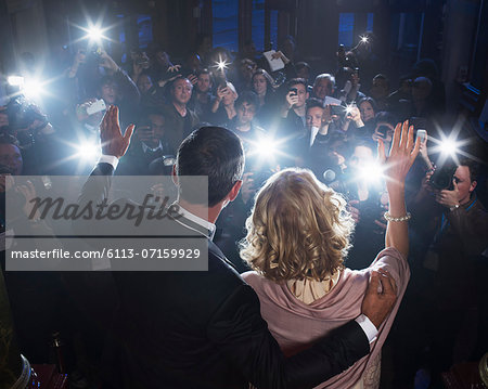 Celebrity couple waving to paparazzi at red carpet event Stock Photo - Premium Royalty-Free, Image code: 6113-07159929
