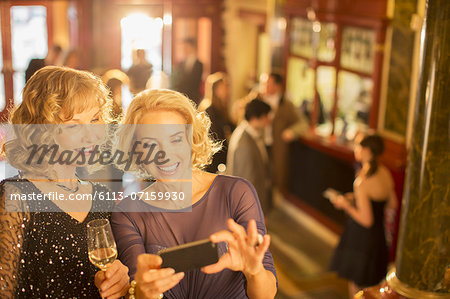 Well dressed women looking at cell phone in theater lobby Stock Photo - Premium Royalty-Free, Image code: 6113-07159930