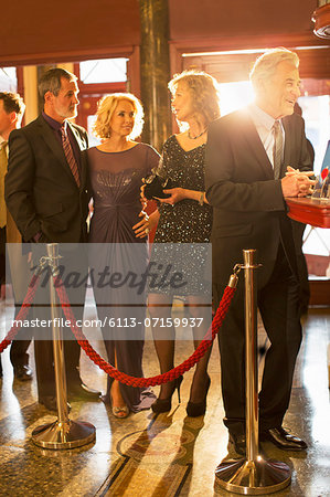 Well dressed couples waiting in bar line in theater lobby Stock Photo - Premium Royalty-Free, Image code: 6113-07159937