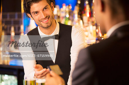 Well dressed bartender taking credit card from customer in luxury bar Stock Photo - Premium Royalty-Free, Image code: 6113-07159945