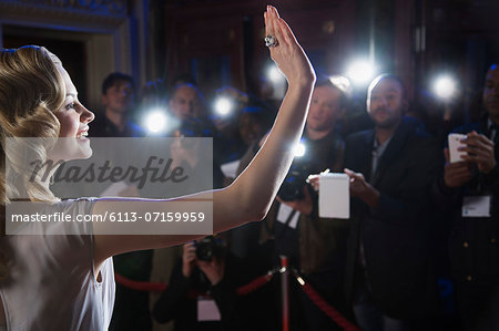 Female celebrity waving to paparazzi at red carpet event Stock Photo - Premium Royalty-Free, Image code: 6113-07159959