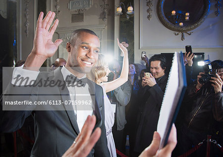 Well dressed male celebrity waving to fans and paparazzi at red carpet event Stock Photo - Premium Royalty-Free, Image code: 6113-07159962
